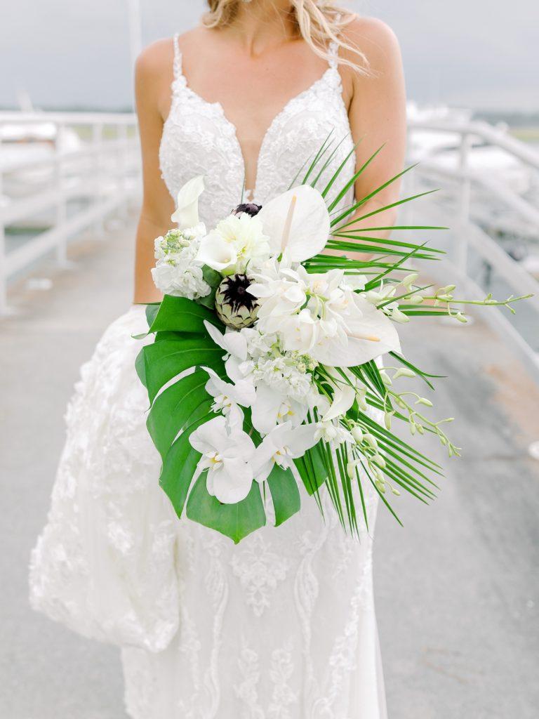 Bridal bouquet with palm leaves, orchids, anthurium and dahlias